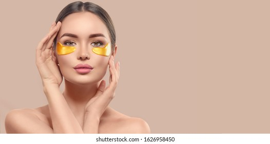 Woman with under eye collagen gold pads, beauty model girl face with healthy fresh skin. Skin care concept, anti-aging moisturizing eye mask, golden hydrogel patches, eye skin treatment, cosmetology