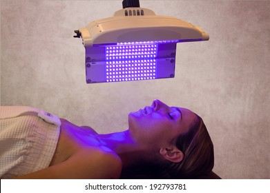 a woman under a light therapy machine, blue light