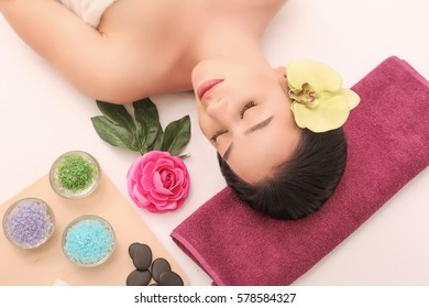 Woman under professional facial massage in beauty spa.