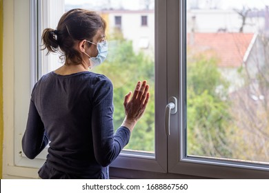 A woman under quarantine at home, wearing a medical face mask and a casual outfit, is standing idle in front of a closed window, the hand on the glass, staring into space.