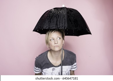 Woman under the umbrella in the rain in studio on the pink background