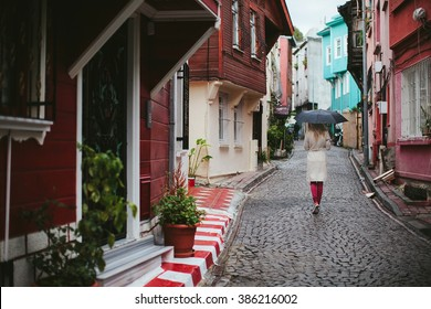woman under an umbrella walks through the old streets of Istanbul