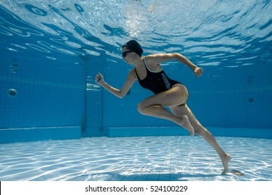 Woman under water runs along the bottom of a swimming pool