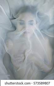 A woman under white fabrics in water