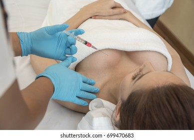 Woman undergoes a cosmetic surgery breast augmentation removal reduction and Doctor hand in gloves surgeon  inject for plastic surgery