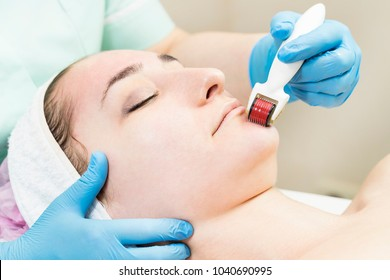 The woman undergoes the procedure of medical micro needle therapy with a modern medical instrument derma roller