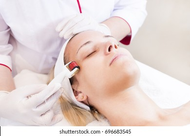 The woman undergoes the procedure of medical micro needle therapy with a modern medical instrument derma roller.