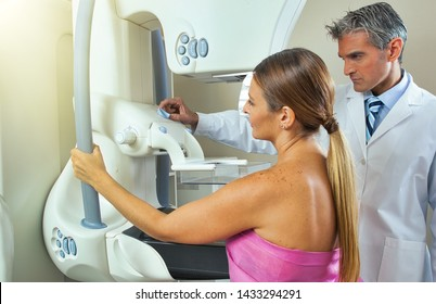 Woman undergoing breast xray under doctor supervision.