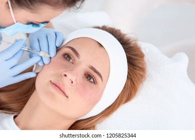 Woman undergoing face biorevitalization procedure in salon. Cosmetic treatment