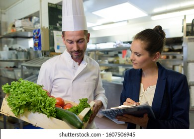 woman undergoing inspection in restaurant kitchen