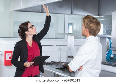 woman undergoing inspection in restaurant kitchen with chef