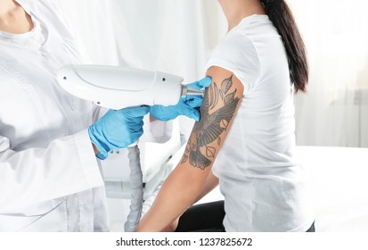 Woman undergoing laser tattoo removal procedure in salon