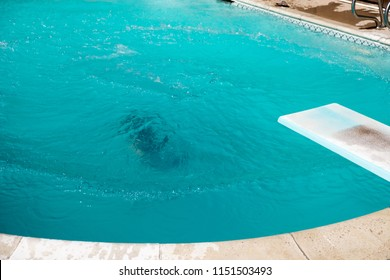 Woman underwater after jumping into a swimming pool from diving board. Girl drowning in pool, Girl submerged underwater in swimming pool.