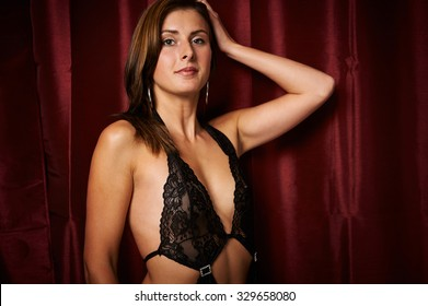 Woman in underwear before red curtain