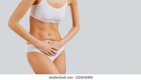 Woman in underwear holding her belly.