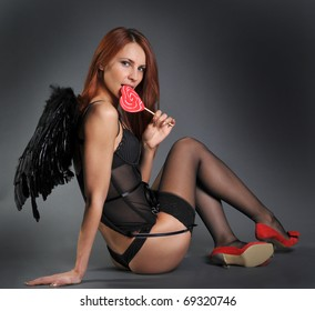 The woman in underwear in a suit of an angel with a sugar candy on a stick in the form of a heart