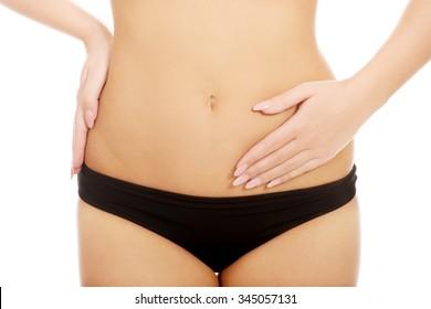 Woman in underwear touching her slim belly.