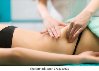 Woman in underwear is under spine massage treatment