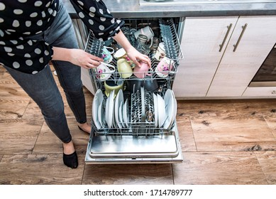 Woman unloading open dishwasher machine in the kitchen. Full dishwashing machine with plates and dishes