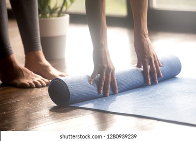 Woman unrolling blue yoga mat to perform yoga asanas safely and comfortably, preparing for working out in fitness club, before or after sport routine, legs and hands close up view. Well being concept