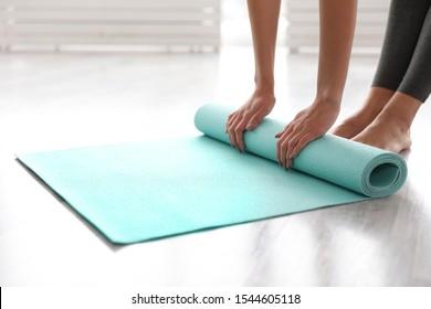 Woman unrolling mat in yoga studio, closeup