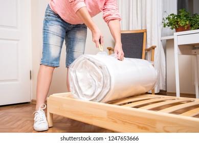 Woman unrolling new Mattress, cutting vacuum package