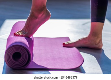 Woman unrolling pink yoga mat with her foot