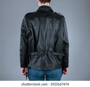 A woman in unzipped black biker leather jacket. Back view. Grey background.