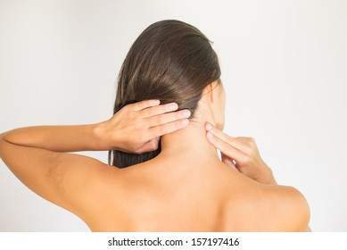 Woman with upper back and neck pain standing naked with her back to the camera and her hand rubbing her shoulder muscles close to the spine