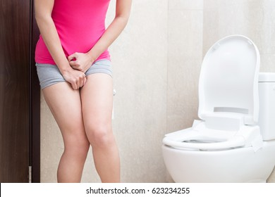 woman with urine urgency in the bathroom