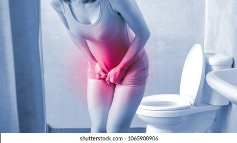 woman with urine urgency in the toilet