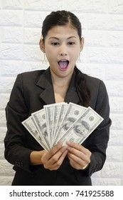 Woman with us dollar money. Business woman holding money. Woman and money. Young pretty woman happy and surprise wow with bank note in hand .