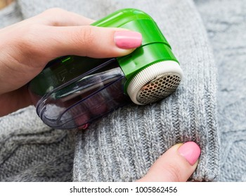Woman use electric device for removing wool and fuzz. Wool shaver.