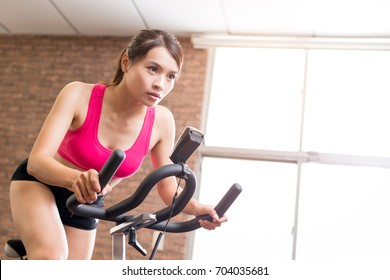 woman use exercise bike and training hard