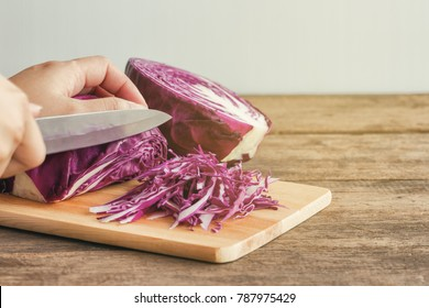 Woman use knife kitchen to chopped or sliced fresh purple cabbage on cutting board to shredded on wood table. Prepare vegetable for cooking cabbage salad or coleslaw. Homemade food concept.