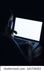 Woman use laptop computer at night. Mockup image of a girl using a laptop with a blank white screen in the dark.