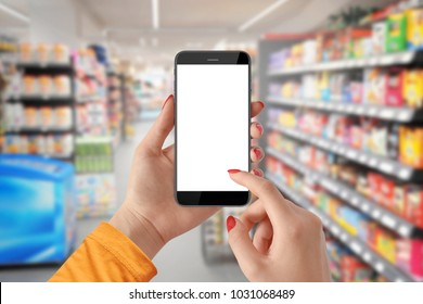 Woman use mobile phone with blank screen, blurred supermarket in background