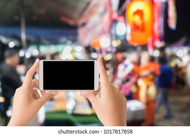 woman use mobile phone and blurred image of japanese street food shop as background