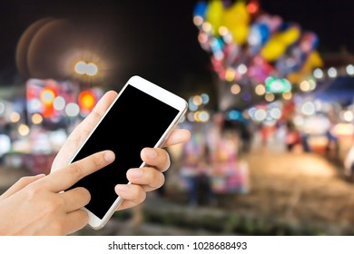 woman use mobile phone and blurred image of people in the temple fair in the country of Thailand