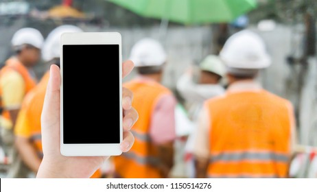 woman use mobile phone and blurred image of the manager and engineers in the construction work site