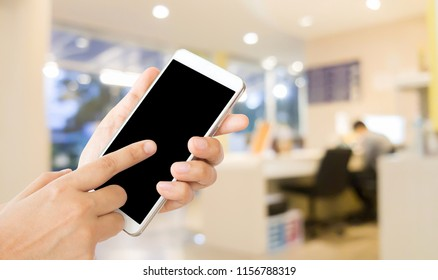 woman use mobile phone and blurred image of reception area of dental clinic