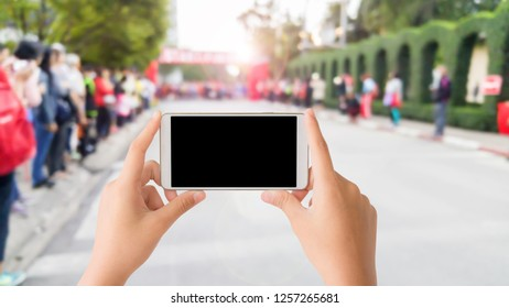 woman use mobile phone and blurred image of the crowd people beside the road of marathon racing at start point