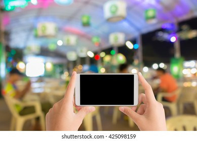 woman use mobile phone and blurred image of people in beer garden at night