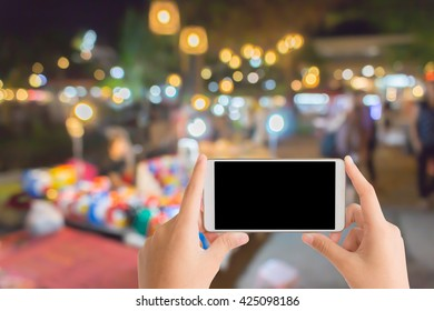 woman use mobile phone and blurred image of street market at night