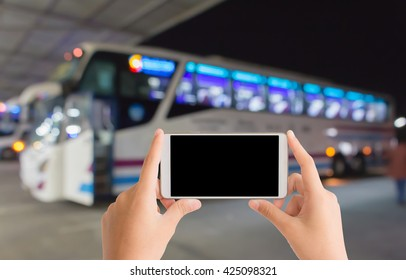 woman use mobile phone and blurred image of bus with beautiful light at night