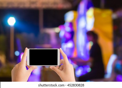 woman use mobile phone and blurred image of women sing on the stage in night party