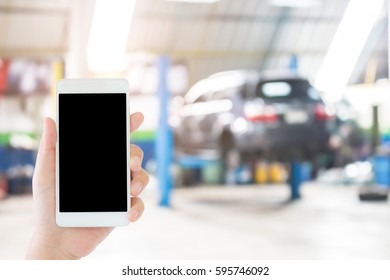 woman use mobile phone and blurred image of the automobile repair shop