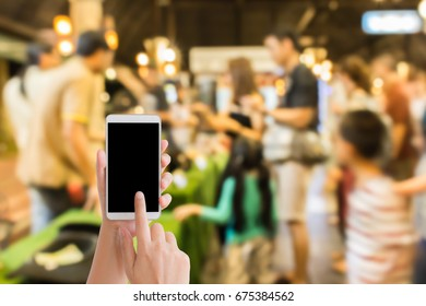 woman use mobile phone and blurred image of people at the animals show in the night street market