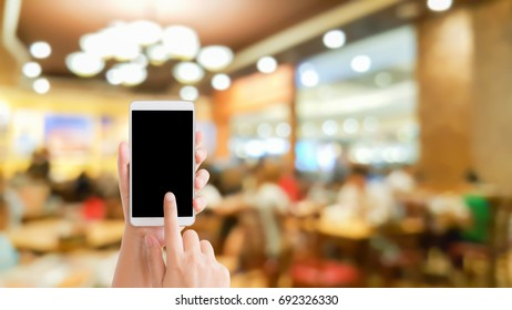 woman use mobile phone and blurred image of people in the restaurant with beautiful bokeh from the lights