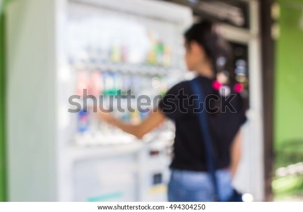 woman use mobile phone and blurred image of a girl by soft drink from beverage vending machine